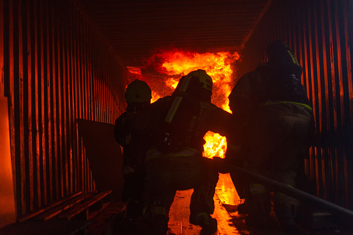Firefighters run towards a burning building to rescue building occupants and contain/extinguish the fire.